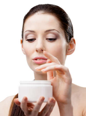 Woman holding cream container and starting to apply face cream, isolated on white photo