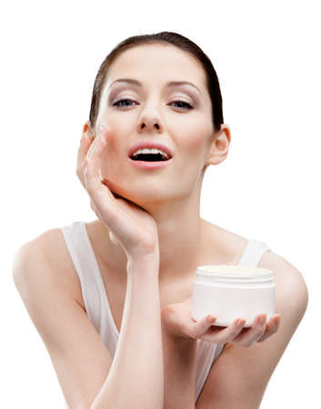 Woman applying cream from container on face, isolated on white. The pursuit of beauty photo