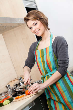woman short hair: Woman in striped apron chops vegetables in the modern comfortable kitchen