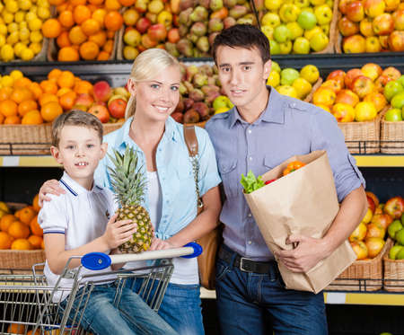 Family against shelves of fruits goes shopping. Father keeps a paper bag with fruits and vegetables, son hands pineapple photo