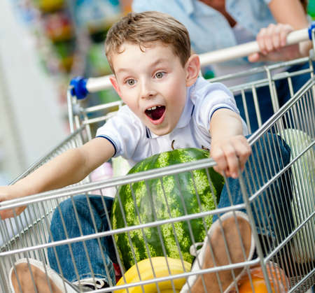 shopping trolley: Boy sits in the shopping trolley with watermelon and other products bought by parents
