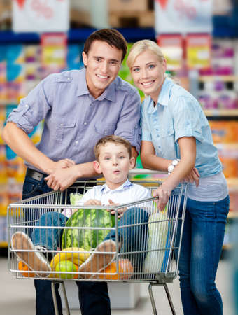 consumerism: Family drives shopping trolley with food and son sitting there with watermelon. Concept of fresh and healthy food and consumerism