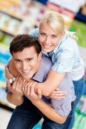 Girl embraces man in the shop. Concept of happy relationship and affection photo