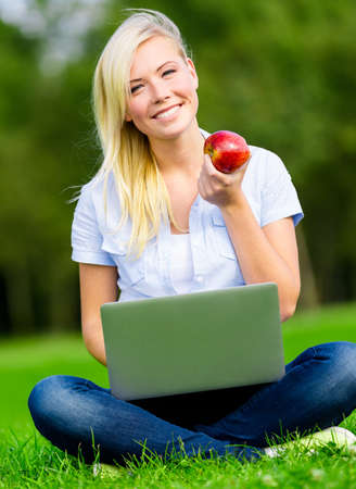 Attractive girl with silver laptop and healthy red apple sitting on the green grass in the summer park photo