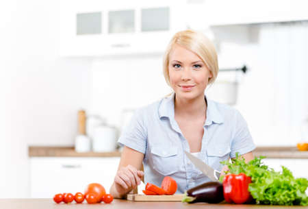 Woman slices groceries for salad sitting at the kitchen table Stock Photo - 23371944