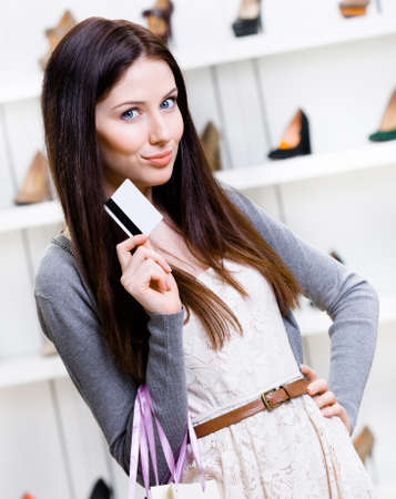 Lady hands credit card in footwear shop with great variety of stylish shoes photo