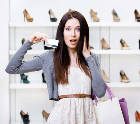 Woman holds credit card in footwear shop with great variety of stylish shoes photo