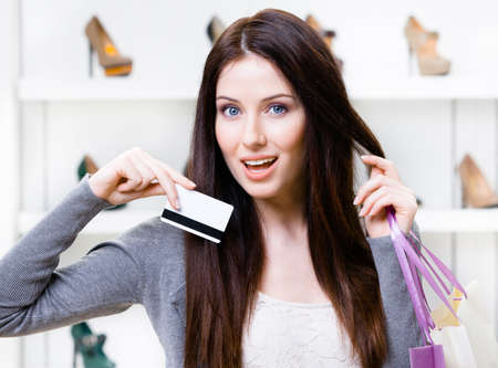 Female keeps credit card in footwear shop with great variety of stylish shoes photo