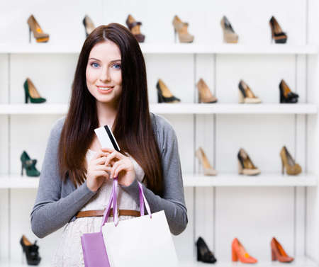 Lady holds credit card in footwear shop with great variety of stylish shoes photo