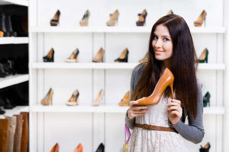tienda zapatos: Retrato de medio cuerpo de la mujer manteniendo zapato de tacón alto de cuero marrón en el centro comercial