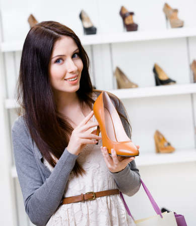 Half-length portrait of woman handing brown leather pump in shopping center photo
