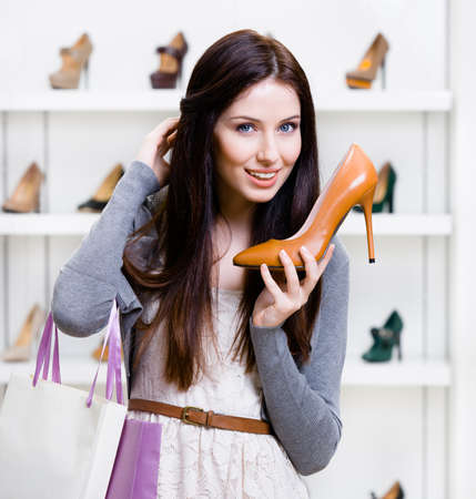 Half-length portrait of woman handing brown leather heeled shoe in shopping center photo