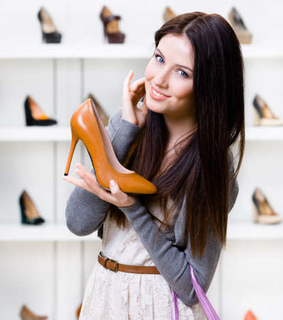 Half-length portrait of woman keeping brown leather stylish shoe in shopping center photo