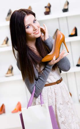 high heeled shoe: Half-length portrait of woman handing brown leather stylish pump in shopping center