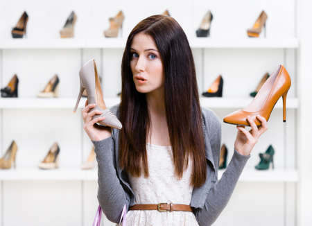 doubtfulness: Woman keeps two pumps in the shopping mall and cant choose the one for her