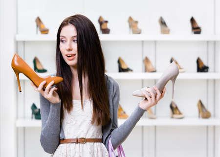 Frau hält zwei hochhackige Schuhe in der Shopping-Mall und kann nicht wählen, die für ihre Lizenzfreie Bilder