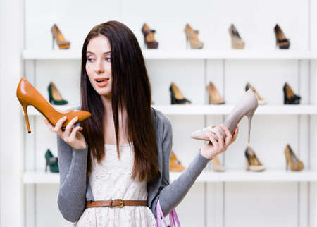 doubtfulness: Woman keeps two high heeled shoes in the shopping mall and cant choose the one for her Stock Photo