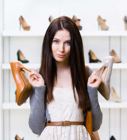 doubtfulness: Woman keeps two heeled shoes in the shopping mall and cant choose the one for her Stock Photo