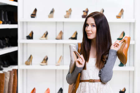 doubtfulness: Woman holds two pumps in the shopping mall and cant choose the one for her