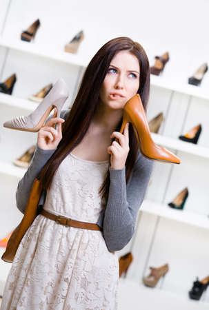 doubtfulness: Woman hands two shoes in the shopping mall and cant choose the one for her Stock Photo