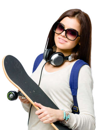 Portrait of teenager with skateboard wearing sunglasses, earphones and rucksack, isolated on white. Concept of young generation Stock Photo - 23371385
