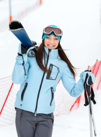 Half-length portrait of woman wearing sports jacket and goggles who hands skis
