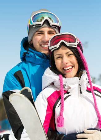 Portrait of couple embracing skiers with skis in hands photo