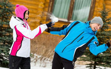 palle di neve: Giovane coppia divertirsi all'aria aperta durante le vacanze invernali e giocare a palle di neve