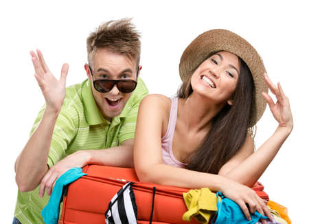 Couple packs up suitcase with clothing for travel, isolated on white. Concept of romantic vacations and lovely honeymoon Stock Photo