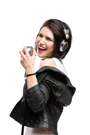 Half-length portrait of rock musician with earphones wearing leather jacket and keeping static mic, isolated on white. Concept of rock music and rave photo