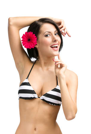 Half-length portrait of woman wearing bikini and flower in hair, isolated on white. Concept of summer holidays and traveling photo