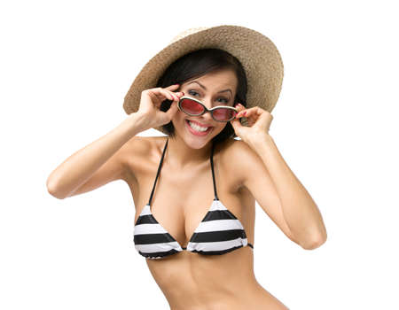 Half-length portrait of female wearing bikini, hat and sunglasses, isolated on white. Concept of summer holidays and traveling photo