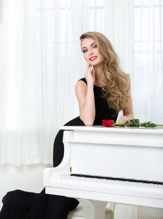 Portrait of woman in black dress standing near the piano with red rose on it. Concept of music and art Stock Photo - 23353237