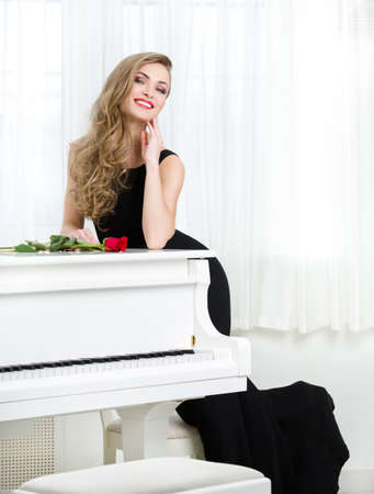 Full-length portrait of woman in black dress standing near the piano with red rose on it. Concept of music and creative hobby photo