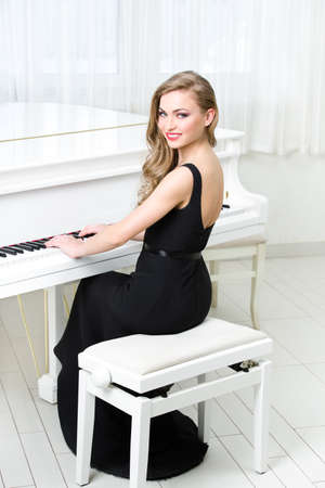 Portrait of woman in black dress sitting and playing piano. Concept of music and art Stock Photo - 23353240