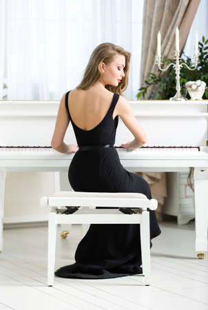 instrumentalist: Back view of woman in black dress sitting and playing piano. Concept of music and leisure