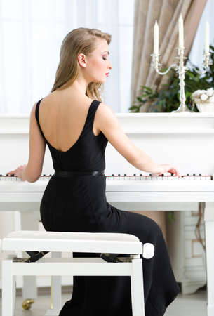 Back view of woman in black dress sitting and playing piano. Concept of music and enjoyment photo