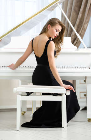 avocation: Back view of woman in black dress sitting and playing piano. Concept of music and art