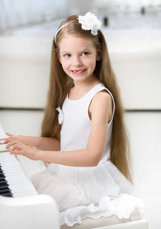 ebony: Portrait of little girl in white dress playing piano. Concept of music study and entertainment