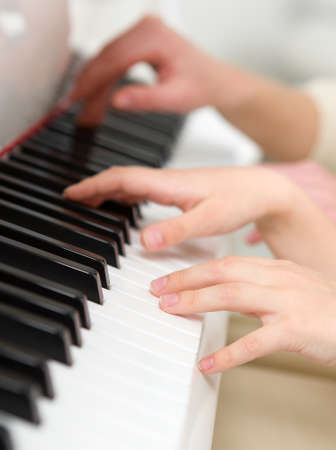 avocation: Close up of hands playing piano. Concept of music and creative hobby
