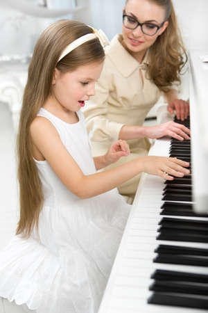 teaches: Tutor teaches little girl to play piano. Concept of music study and enjoyment