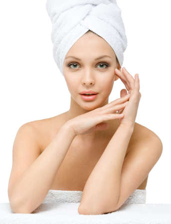 Girl with towel on head touches her face, isolated on white. Concept of healthcare, beauty and youth photo