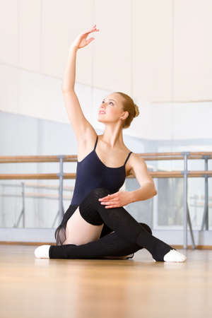 Ballerina works out sitting on the wooden floor in the classroom with barre and mirrors photo