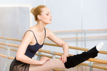 barre: Ballet dancer stretches herself near barre and mirrors in the dancing hall Stock Photo