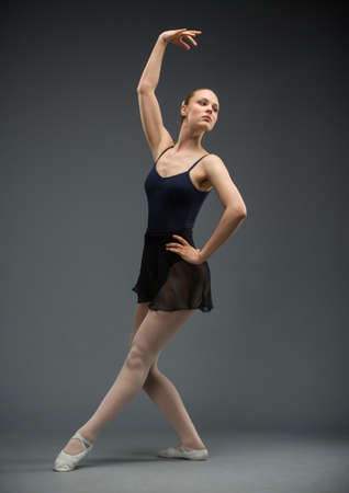 Full length of dancing ballerina, isolated on grey. Concept of elegant art and sportive hobby photo