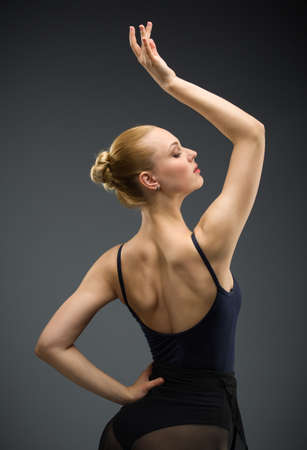 Half-length portrait of dancing ballerina with hand up, isolated on grey. Concept of elegant art and sportive hobby photo