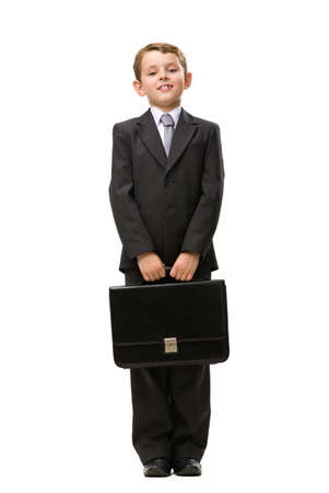 Full-length portrait of little businessman keeping black case, isolated on white. Concept of leadership and success photo