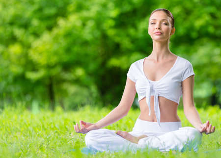 Woman with closed eyes sits in asana position zen gesturing. Concept of healthy lifestyle and relaxation Stock Photo - 23353525