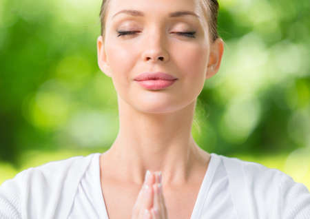 keep fit: Close up of woman with eyes closed prayer gesturing. Concept of healthy lifestyle and Buddhism Stock Photo