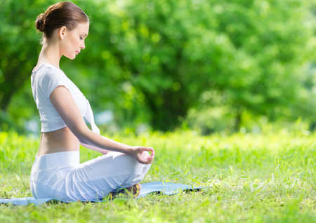 sideview: Profile of woman who sits in lotus position zen gesturing. Concept of healthy lifestyle and relaxation Stock Photo